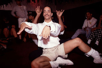 Dancer Cesar Valentino. Latinx man wearing white shirt and boots, beige shorts dances with hands.