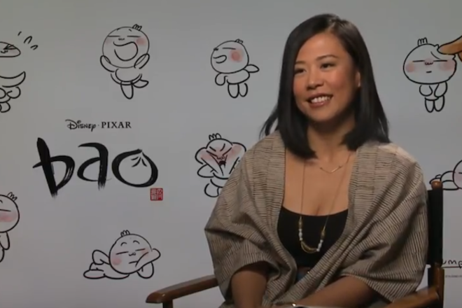"""Domee Shi. Asian woman in tan shirt with black tank top and long, black bob hair smiles at camera, while sitting in front of a white backdrop that says """"Bao"""" and features drawings of an animated dumpling"""