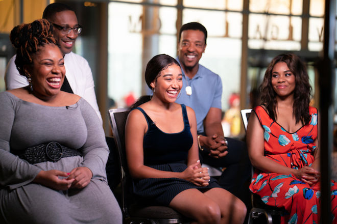 """Angie Thomas in grey dress smiles in front of George Tillman Jr. in white shirt next to """"The Hate U Give"""" cast in multicolored clothing, seated three to a row in two rows in front of grey background"""
