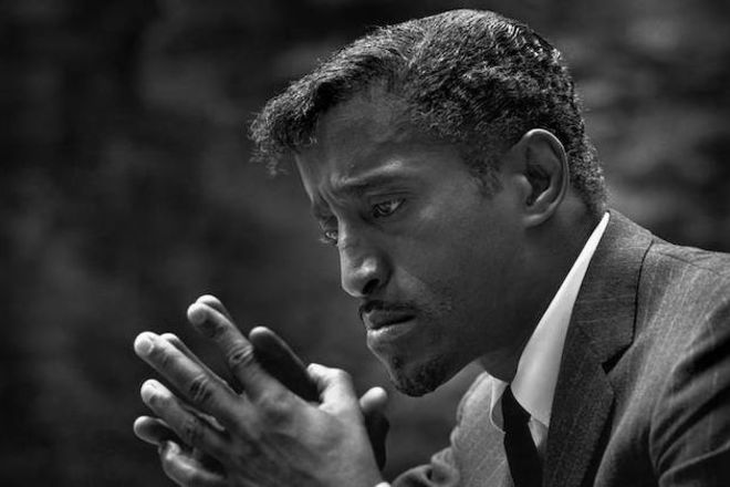 Sammy Davis Jr. Black-and-white photograph of Black man in suit with black tie and white shirt staring at hands in front of curtain.