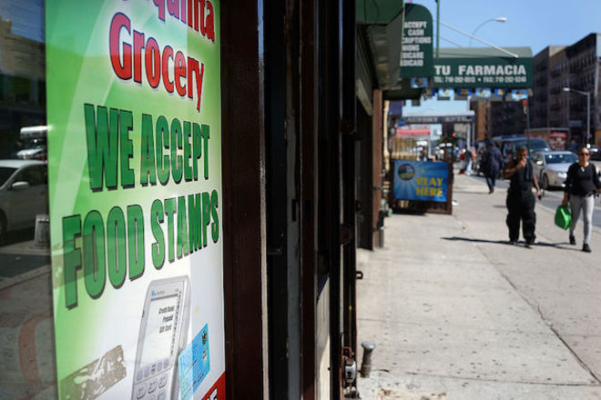 Bronx store window with sign about food stamps