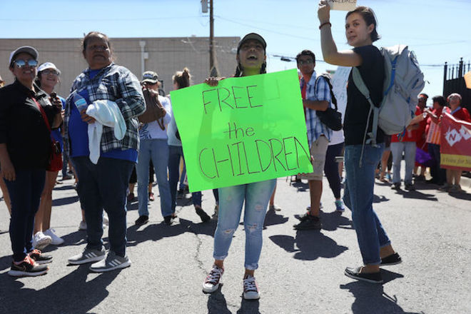 """Woman wearing ripped blue jeans and a baseball cap stands with a group of people on the street as she holds a green sign that says, """"Free the children."""""""