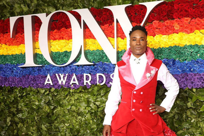 Billy Porter. Black man with short dark hair in front of Tony Award sign, wearing red and white tuxedo-style dress with tulle.