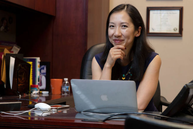 Leana Wen. Asian woman wearing a black sleeveless shirt, sitting behind a desk with a laptop computer on a brown desk.