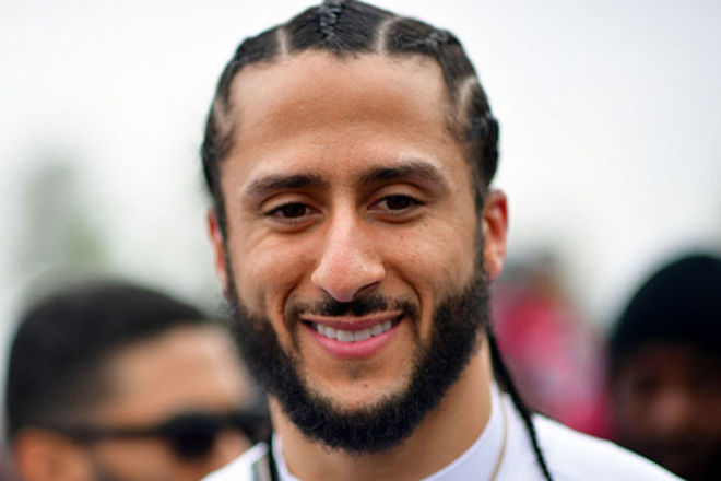 Colin Kaepernick. Black man with cornrows and facial hair wearing white fitted jersey.