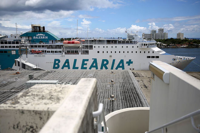 """Balearia ferry docked in Florida. White ferry with blue writing that reads """"Balearia"""" on it against a blue sky with white clouds"""