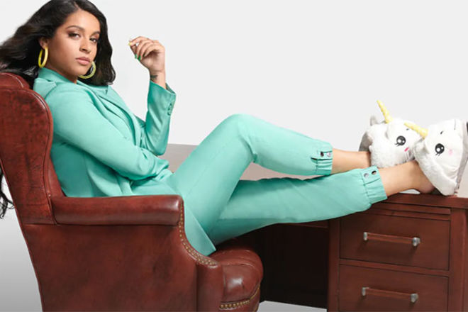 Lilly Singh. South Asian woman with long dark hair wearing a mint green suit and white unicorn slippers.