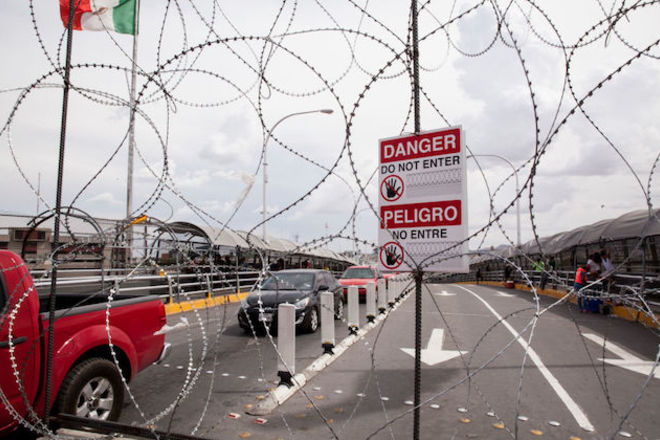 """Razor wire is strung along the U.S. and Mexico sides of a port of entry in El Paso, Texas, along with a sign that reads """"Danger, do not enter."""""""