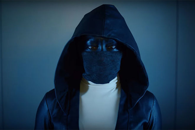 """""""Watchmen."""" Black woman dressed in all black, mask and cape."""