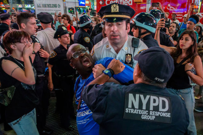 A black man wearing a blue jersey is violently handcuffed and arrested by two white police officers.