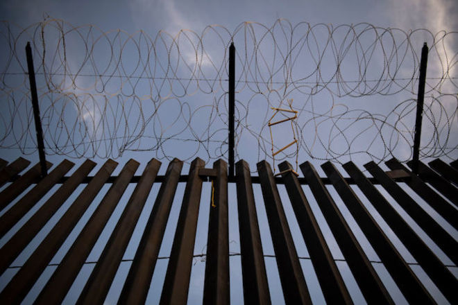 A shot looking up at black painted fence with barbed wire at the top.
