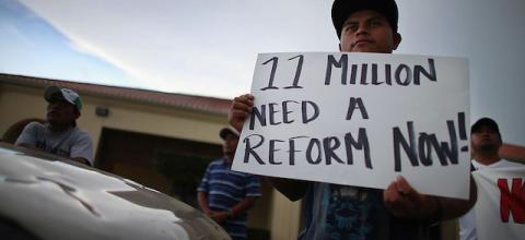 """Man holds sign: """"11 million need a reform now!"""""""