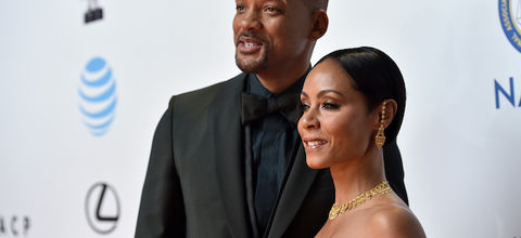 Black man in black suit with dark blue shirt next to Black woman in teal dress and gold jewelry against white background