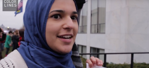 A young woman in a royal blue hijab smiles while being interviewed at the Women's March on Washington