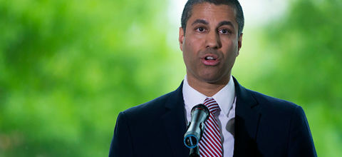 Brown man in navy suit red-and-blue-striped tie in front of green trees and grey sky
