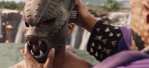 A Black man places a bronze mask in the shape of a cat onto the face of a younger Black man