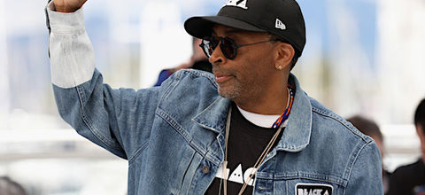 Black man with grey goatee holds up fist while wearing black sunglasses and hat with white text and black shirt with white text under blue and grey jean jacket in front of