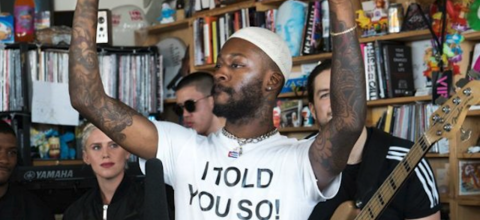 Black man in white shirt with black text and white hat in front of people in black clothing and brown bookshelf with multicolored books