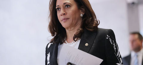 Kamala Harris. Brown woman with brown hair in black blazer with white embroidery and shirt and necklace holding white paper and black folder in front of gray wall