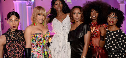 """Cast of """"Pose"""" and Janet Mock in multicolored outfits in front of room bathed in purple light"""