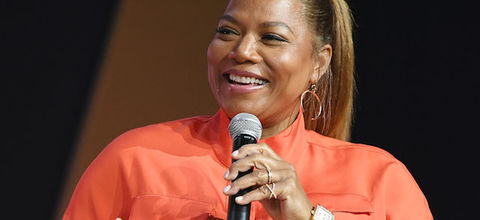 Queen Latifah in orange shirt holding black microphone in front of black and orange wall