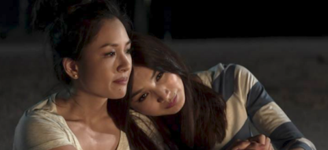 Constance Wu in white shirt sits and holds hands with Gemma Chan in blue-and-white-striped shirt in front of brown beach sand and black night sky
