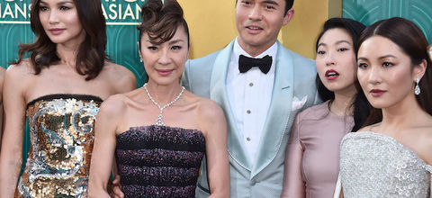 """Cast of """"Crazy Rich Asians"""" in multicolored dresses and suit in front of gold and green background"""