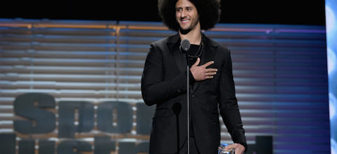 """Colin Kaepernick. Black man with black afro and beard stands in black suit with black t-shirt and necklace while holding glass award behind black microphone and stand and in front of blue and brown background and grey letters that read """"Sports Illustrated"""