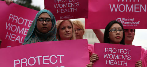 """Women hold pink signs with white lettering. They read, """"Stand with women,"""" and """"Protect women's health."""""""