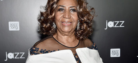Aretha Franklin. Black woman with brown and blonde hair smiles in white dress in front of black wall with white text
