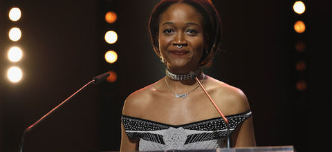 Kimberly Drew. Black woman with black and brown dredlocs and silver septum ring in grey and black dress behind glass podium with black microphone in front of brown wall with orange and yellow lights