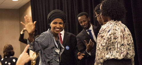 A Black Somali woman waves and smiles at the camera after winning election with three Black supporters standing behind her in a room with a black curtain in the background