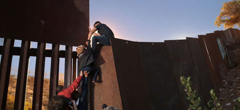 Members of the migrant caravan climb over the U.S.-Mexico border fence while crossing into San Diego, California, from Tijuana, Mexico, on December 3, 2018.