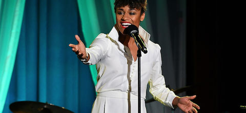 Ariana DeBose. Black Latinx woman with black hair in white outfit sings into black microphone on black stand in front of blue curtain and green lights