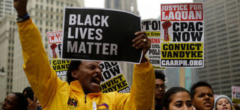 "Black man in yellow jacket with fist up, holding black and white sign that reads, ""Black lives matter."" Crowd surrounds him."
