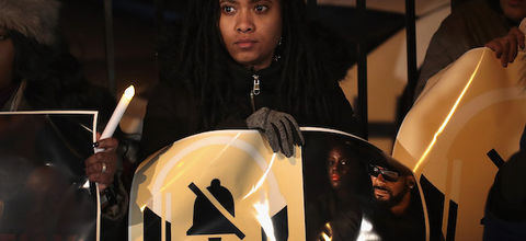 "R. Kelly. Black woman with black dredlocs stands in black coat and holds white protest sign with black text that spells ""#MuteRKelly"" and image of Black man in black sunglasses and hat and shirt."
