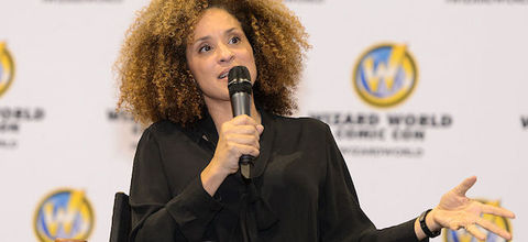 Karyn Parsons. A Black woman with mid-length, natural curly sitting in front of a blurred out white background sponsored by Comic Con.