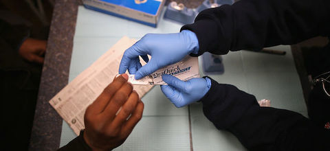 A pair of blue-gloved hands gives a white stick to a pair of Black hands. Light blue paper lines the table below, a blue and white box of gloves sits on the table