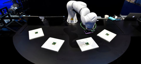 white robotic arm on a table with four squares in front