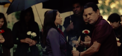 White woman faces a Latinx man with women holding flowers behind her