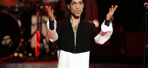 A Black man stands on a stage wearing black and white with his hands outstretched.