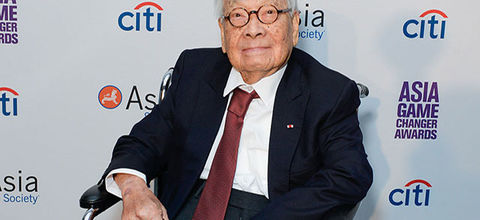 I.M Pei. Elder Asian man in black suit, red tie, black glasses, seated in wheelchair  in front of step and repeat.