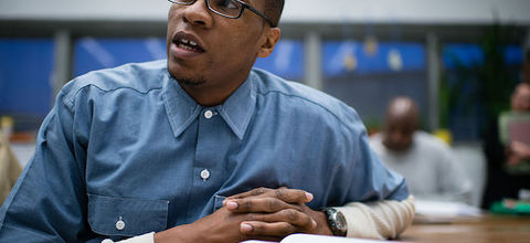 Black man wearing blue shirt and black glasses sits with his hands folded.