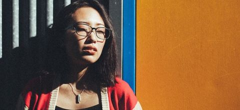 Asian woman wearing black-rimmed glasses and red cardigan with off-white ribbing and sleeves stands in front of corrugated metal wall with orange painted wall beside it