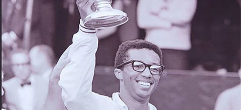 Arthur Ashe. Black and white photo of young Black man, wearing glasses and white top, holding up a trophy.