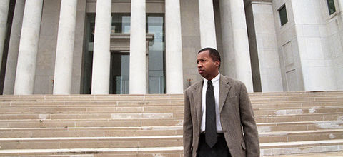 Bryan Stevenson. Black man in gray jacket suit, black pants and tie, white shirt, standing on the steps of a courthouse.