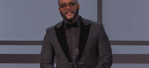 Tyler Perry. Black man with low hair, glasses, wearing gray tux and black tuxedo.