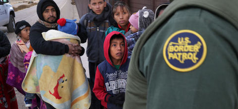 Border patrol agent wearing green uniform stands before a group of migrant children and their guardian.