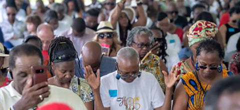 Black pilgrims. A group of Black people with heads down and hands up in prayer.