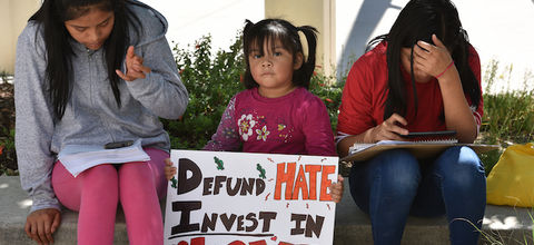 "A young Brown girl sitting between two older Brown girls holds up a sign that says, ""Defund Hate. Invest in Love"""